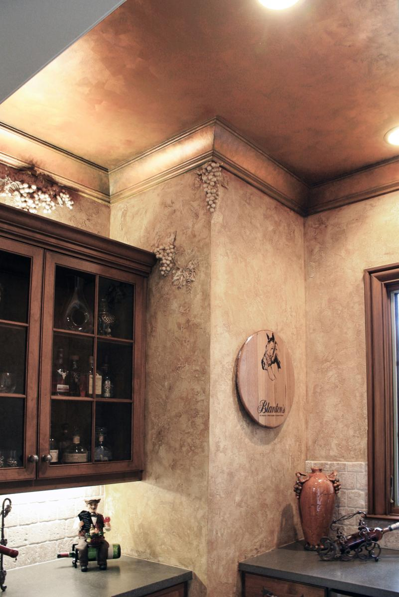 Faux sculpted grapes over European plastered walls in this wine rooms Liquor cabinet on with faux copper ceiling.