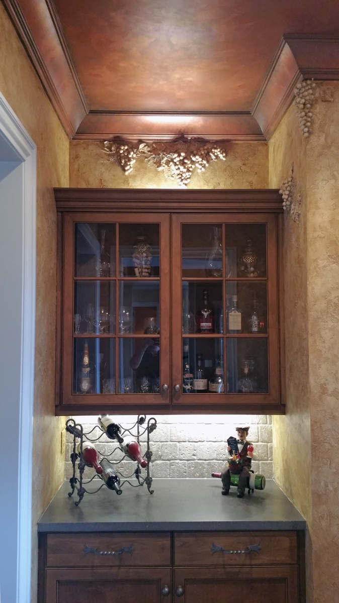 Brentwood customer's butler's pantry converted into a stunning Bourbon and wine room with Tuscan plaster walls sculpted grapes motifs and faux copper ceiling.