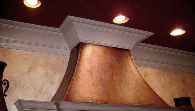 warm colored cabinet glazing with faux copper stove hood.