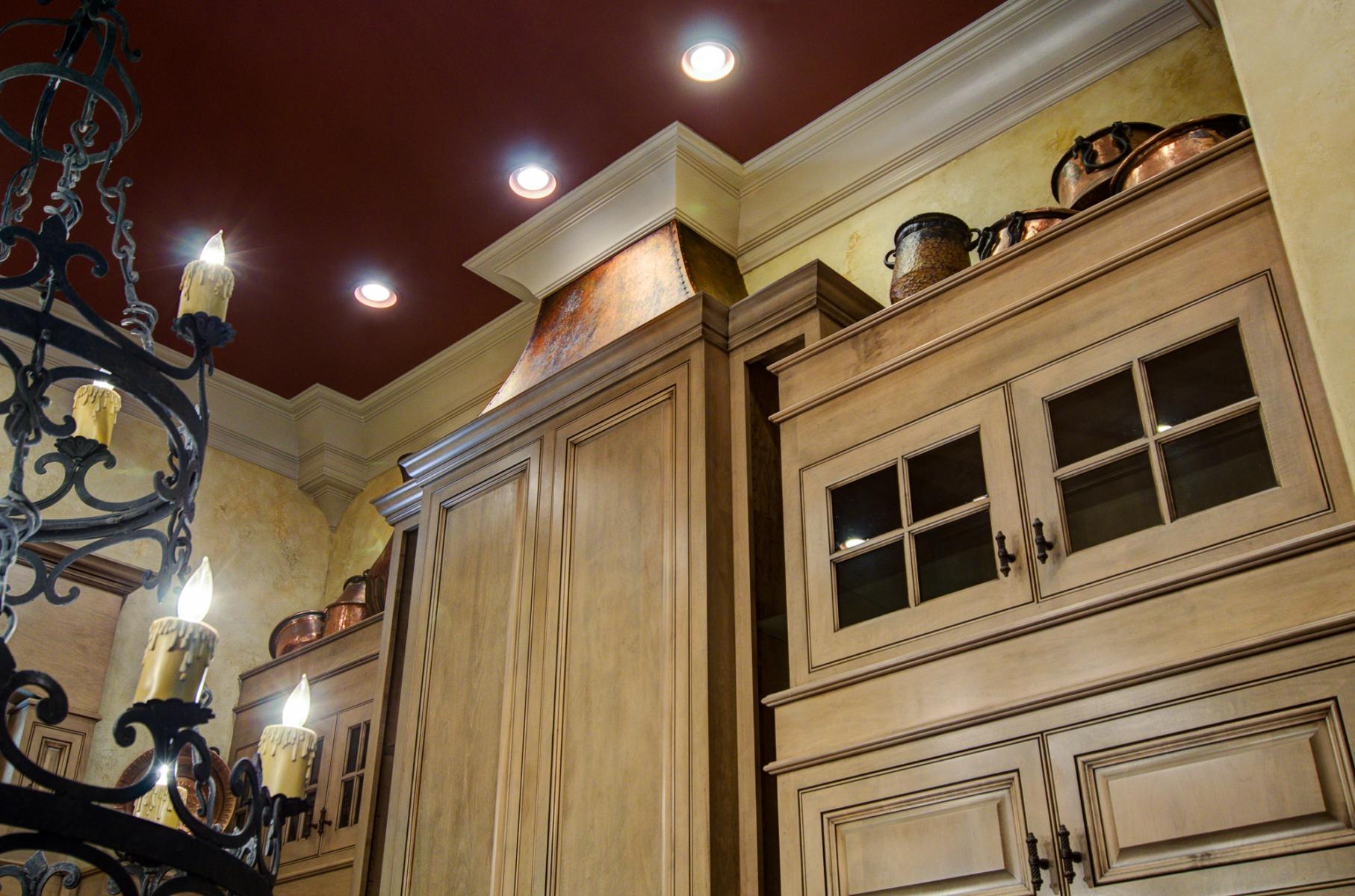 Tuscan colored plaster walls set against warm cabinet glazing and accented with a faux copper stove hood.