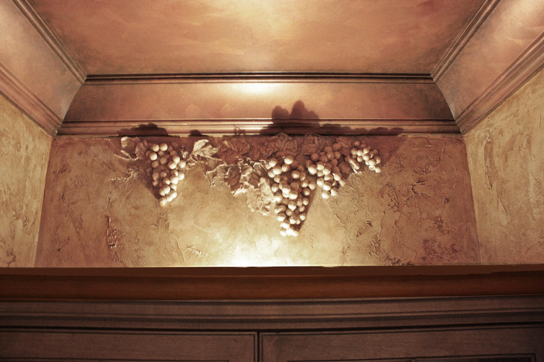 Faux grapes over sculpted over bourbon and wine cabinet.