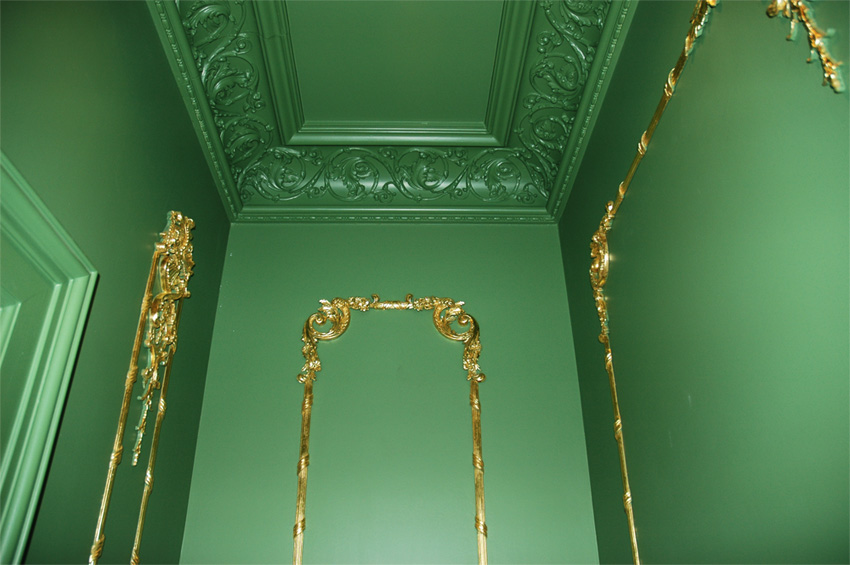 Gold leaf on millwork trim over Russian green colored panels.