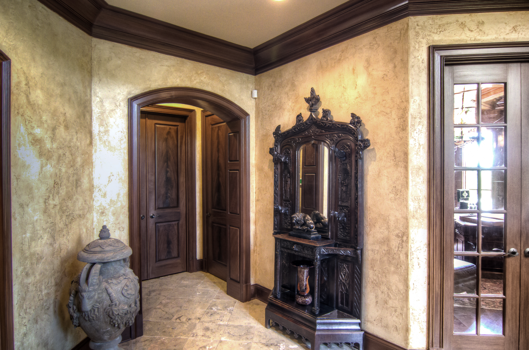 European plaster walls with wood glazed trim and faux mahogany master bedroom entrance doors.