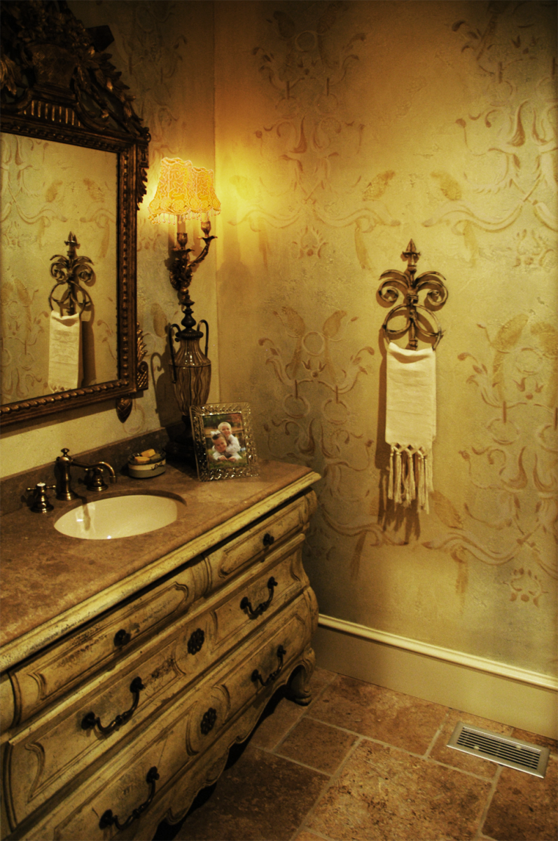 Guest Bath Makeover – Done in tone on tone custom free-hand wall pattern design over a custom colored base coat is the perfect complement to the facsimile vanity piece and stone flooring.