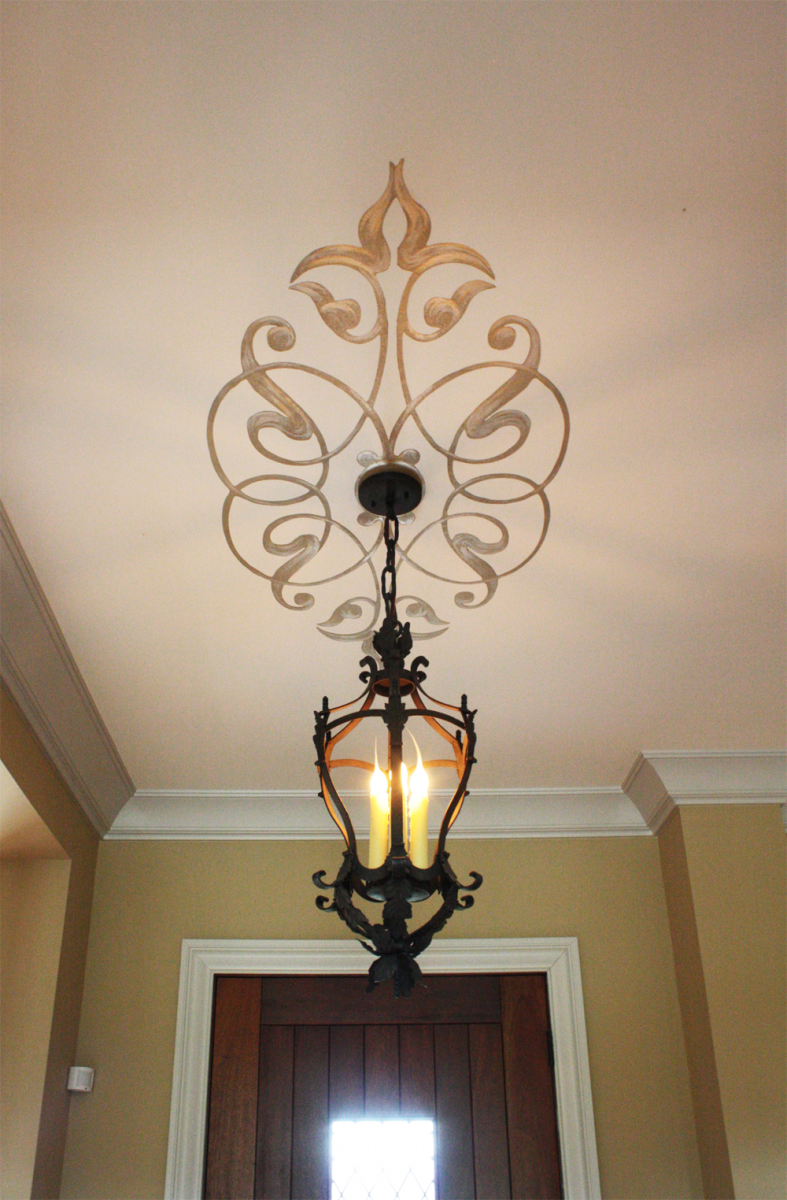 Hand painted ceiling design with gold and silver flourishes.
