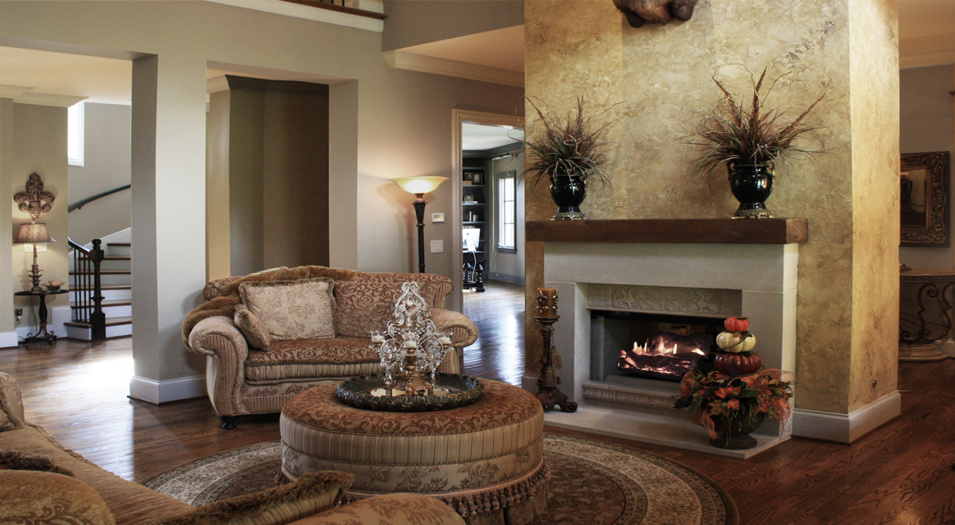 Custom great room wall color with a rustic faux plaster feature wall and faux wood ceiling beams.