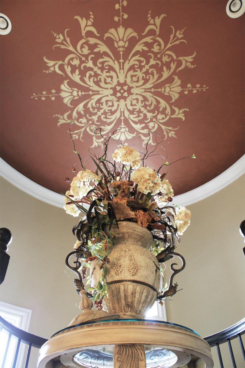 Custom hand painted ceiling stencil with warm toning over glaze close up.