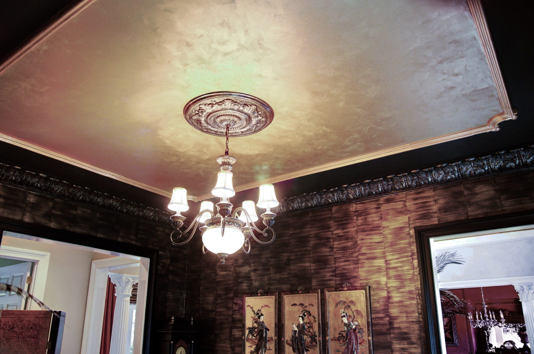 Black woodwork with gold faux bamboo walls and faux metal plaster cornice above.