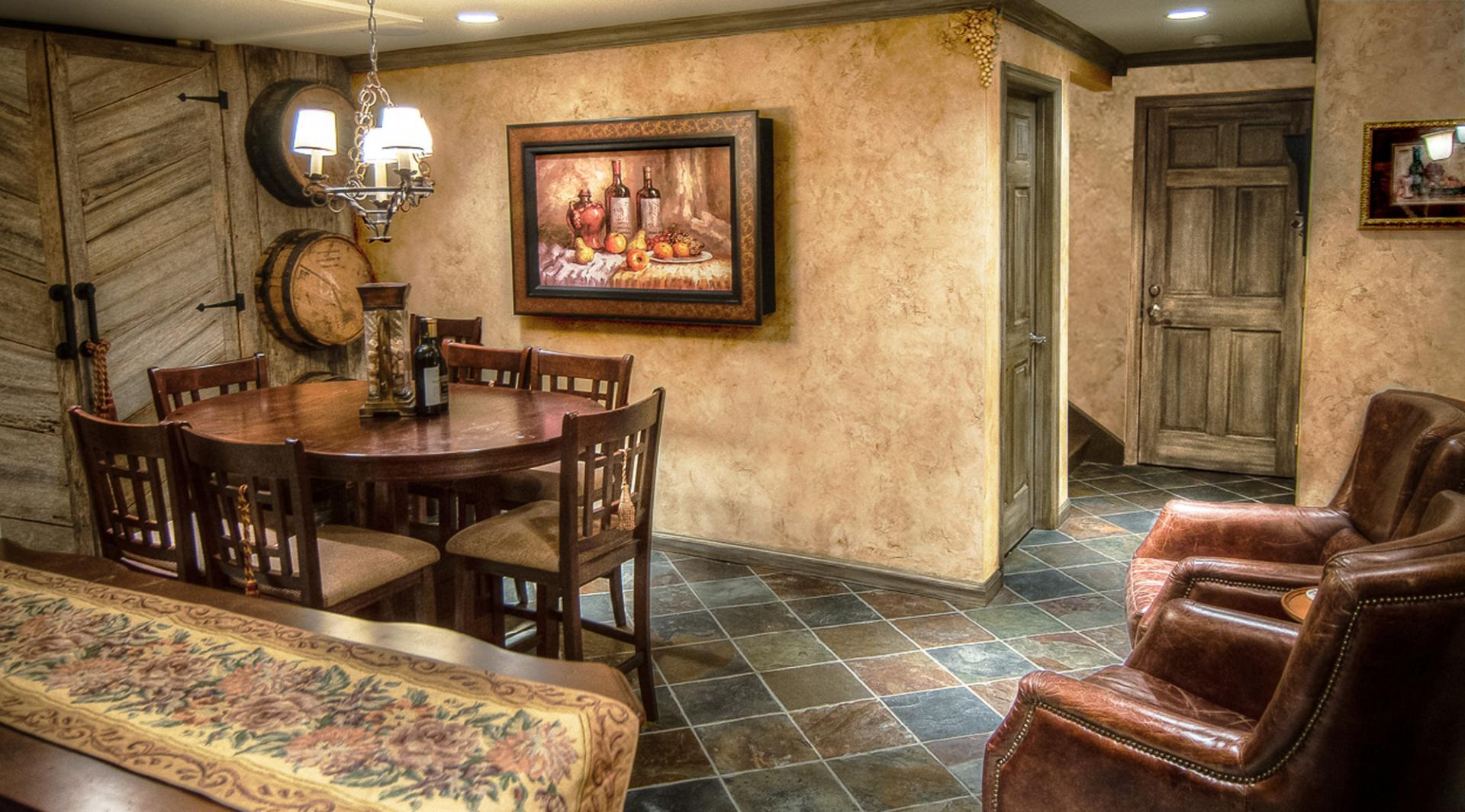 Wine Tasting Room Makeover - Tuscan plaster walls, chiseled grape motifs and faux finished barn siding trim and doors.