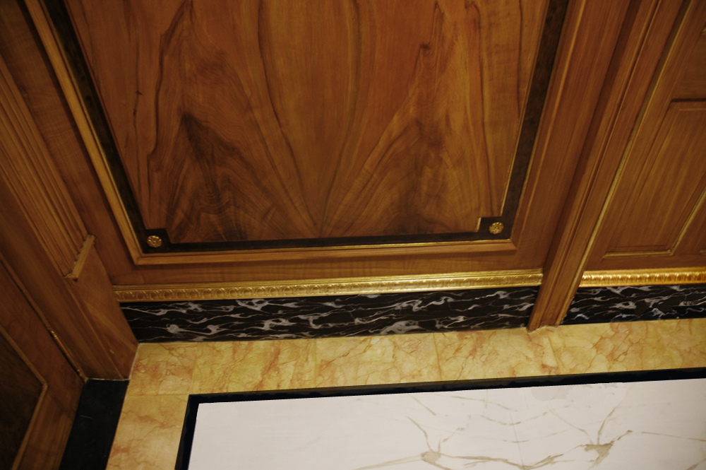 Close-up - Faux picture grained wood walls, faux Portoro marble base, and faux marble inlay flooring, with 23 karat gold leaf accents.