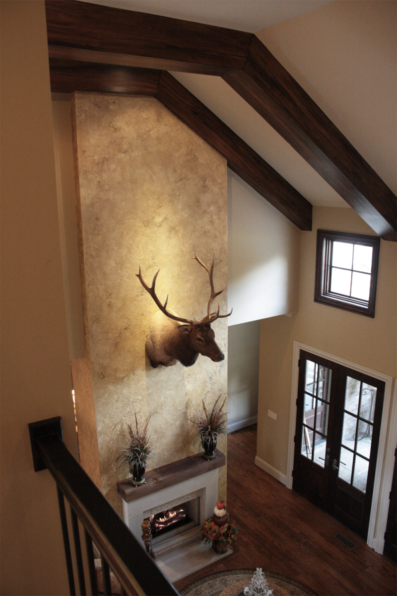 Beautiful wall color and feature wall plaster faux design and faux wood ceiling beams.