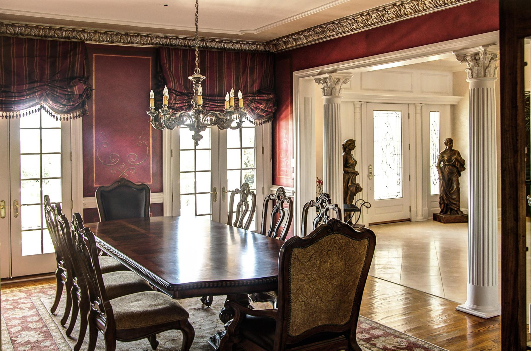 Stencil designs over wine colored walls with a faux metal plaster cornice and chandelier topped with an accented ceiling. Stunning!