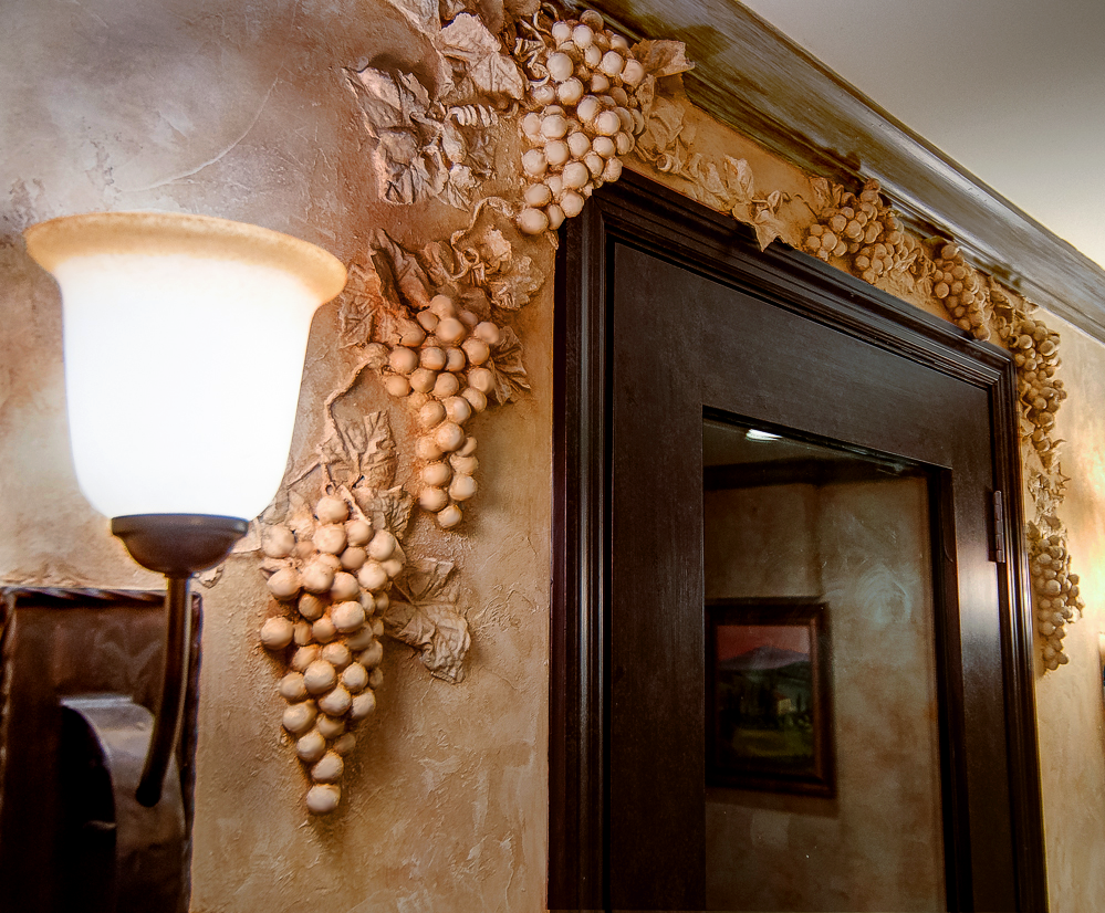 Faux Chiseled Grape Motif - embedded in the Tuscan plaster walls around wine cellar entry door.